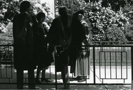Group of four convocation graduates standing outside with Bert Nesbitt - Spring 1986