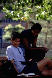 Promotional photograph of two students sitting in the Quad