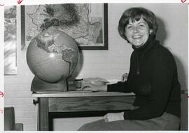 Barabara Farrell poses with globe in Library