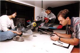 Promotional photograph of three students working on a model airplane