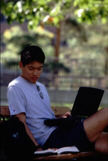 Promotional photograph of a student with laptop in the Quad, 1997