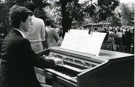 Organist playing outdoors for spring convocation ceremony, 1986