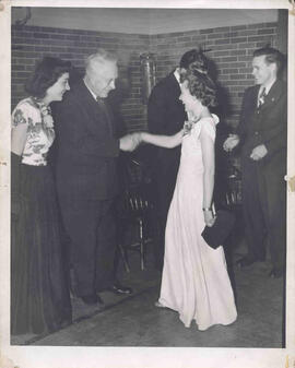 Faith Avis and H. M. Tory greeting people as they enter the building for a social gathering [1945...