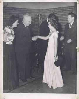 Faith Avis and H. M. Tory greeting people as they enter the building for a social gathering [1945-1946].