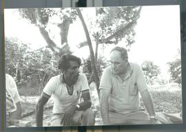Two men sitting under a tree. Likely El Salvador, ca. 1986