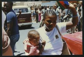 Young mother with SWAPO flag and child celebrate.