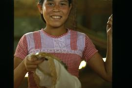 Unidentified girl in a dress with needle and thread embroidering a cloth. Honduras, ca. 1985.