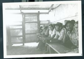 A group of men sitting inside of a shelter. Honduras, ca. 1985