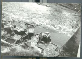 Women washing clothing in basins by a river under a bridge. Likely El Salvador, ca. 1986