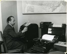 """Ron Nickerson"" sitting before a teletype machine, ca. 1950"