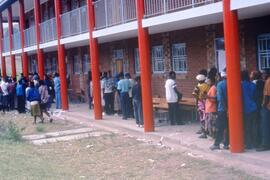 Overcrowded polling station in which both voter card issuing and voting occur in dubious fashion ...