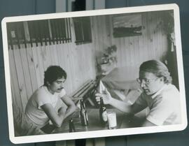 Meyer Brownstone with another man sitting at a table with beer. Honduras, 1985 mission to the Col...