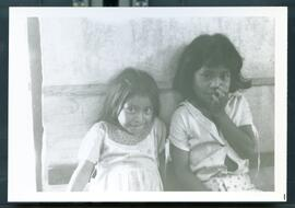 Two young girls sitting in front of a shelter. Honduras, ca. 1985