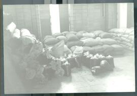 A cellar or room with stack of sacks and plastic bags. Likely El Salvador, ca. 1986