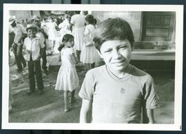 A child in front of a group of people. Honduras, ca. 1985.