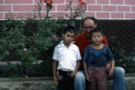 Unidentified man with two children in front of rose bushes and a red brick wall. Honduras, ca. 1985.