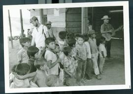 A group of children gathered outside of a shelter. Honduras, ca. 1985.