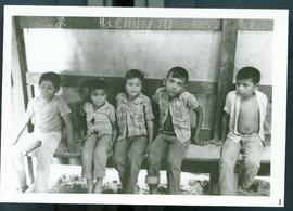Five boys sitting on a bench in a temporary shelter at a refugee camp. Honduras, ca. 1985.