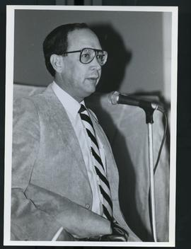 An unidentified man speaking at a microphone.