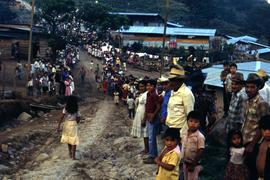 Hundreds of people lining a dirt road, perhaps to watch a procession. Honduras, ca. 1985
