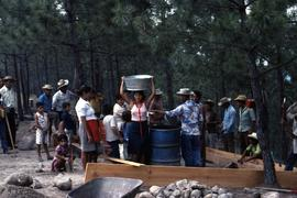 Typically the men lift the tubs and other containers but the women do all the carrying-the more difficult part of the water supply system. Colomancagua, Honduras, ca. 1985