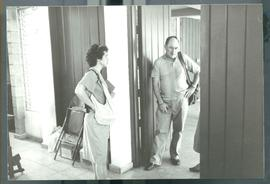 A man and a woman by a door, possibly in a hotel. Likely El Salvador, ca. 1986
