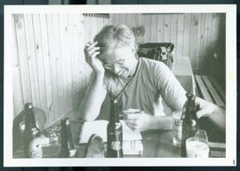 Bruce Cockburn writing in a book at a bar of restaurant. Honduras, ca. 1985.
