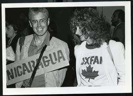 "Bruce Cockburn with unidentified Oxfam Canada member, holding a sign that say ""Nicaragua""."