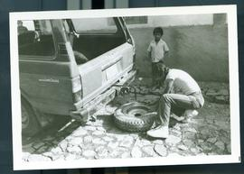 Fixing a flat tire on a land cruiser. Honduras, ca. 1985.