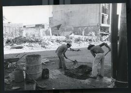 Two men working with shovels in the street in front of a destroyed building. El Salvador, ca. 1986