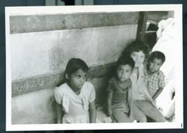 Four children sitting on a bench. Honduras, ca. 1985.